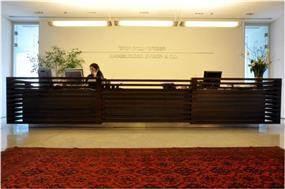 """משרדי המבורגר עברון עו""""ד בתכנון אנדרמן אדריכלים, דלפק קבלה מעץ, שטיח אדום"""
