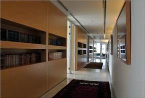 """משרדי המבורגר עברון עו""""ד, בתכנון אנדרמן אדריכלים, מסדרון,ספריית ספרים שקועה בקיר כנישה."""