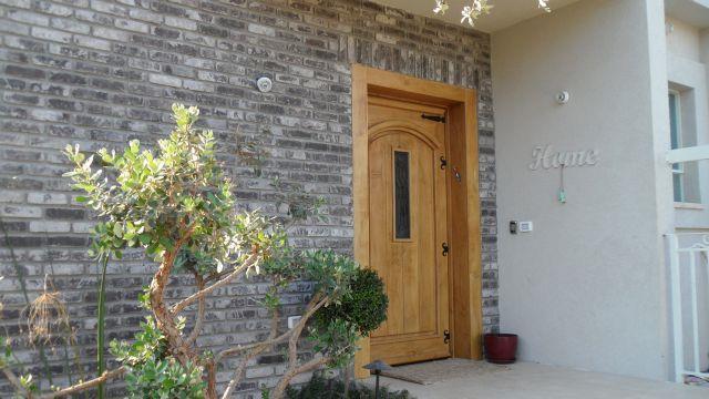 דלת כניסה ומסביבה קיר בריקים, עיצוב האדריכל דרור נח