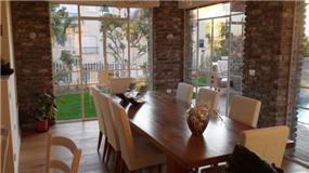פינת אוכל המוקפת חלונות בלגיים וקירות בריקים בעיצוב האדריכל דרור נח