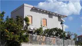 חזית בית עם טיח אפור בשילוב עץ, בעיצוב האדריכל דרור נח