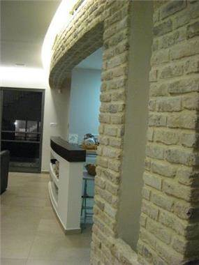 קיר אבן פירוק מתעגל בסלון-אדריכלית, שגית גולדשמידט