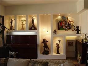 קיר גבס בסלון מעוצב כנישות לתצוגת חפצים.
