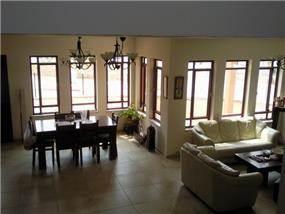 מיקצב של חלונות שוטף את החלל באור, מבט אל הסלון ופינת האוכל.