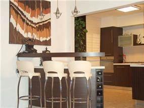 מטבח פתוח/סגור, דלפק אכילה עם כסאות בר,  תמונת קיר גדולה.