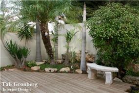 פינה בגינה ריצוף דק ספסל ישיבה מאבן, פינת צמחיה טרופית.