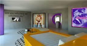 חדר שינה מעוצב ומיוחד, בסיס מיטה בצבע צהוב חרדל, תמונות קיר ענקיות עם מסגרות סגולות.