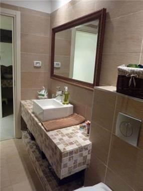 חדר אמבטיה כיור מונח על משטח מרוצף בקרמיקה- פנטהאוז בהוד השרון