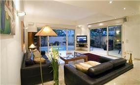 וילה בהרצליה פיתוח - מבט לסלון ולחוץ -סגנון מודרני חם