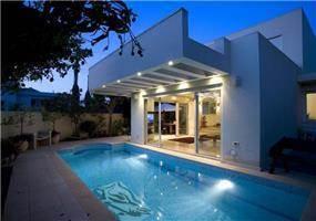 מבט לחזית הבית והבריכה - בית בהרצליה פיתוח בסגנון מודרני נקי וחם