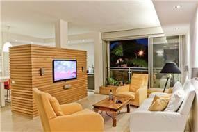 סלון דירה בבבלי המשלבת קיר טלוויזיה מעץ. עיצוב: שמרית קאופמן