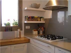 מטבח בסגנון נקי וקלאסי, הכולל חיפוי קיר כהה. עיצוב: שוש פנקס
