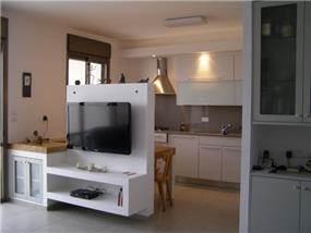 מבט מהסלון לכיוון המטבח. נישת גבס נתנה פתרון טוב לתליית הטלוויזיה וליצירת גבולות בין המטבח והסלון. עיצוב: שוש פנקס