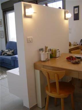 מטבח בהרצליה הכולל נישת גבס עם תאורה לחציצה בין פינת האוכל והסלון ולתוספת תאורה. עיצוב: שוש פנקס