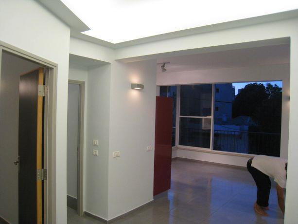 מבואה בדירה תל אביבית, תקרה מוארת בתאורה ניסתרת להדגשת איזור המבואה
