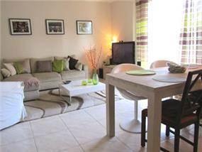 מבט אל פינת האוכל והסלון שעוצבו בסגנון מודרני בשילובי צבעים של אפור, ירוק וסגול. גרונר קטרין CDGECO