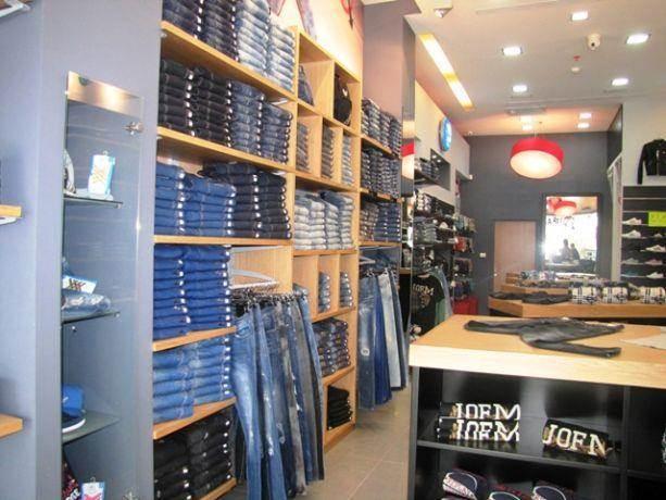 קיר בחנות בגדים המשולב מדפים מודולרים וקבועים. שלומית בן-צור תכנון ועיצוב פנים