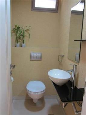 חדר אמבטיה מעוצב בסגנון מודרני הכולל אסלה תלויה וכיור מונח. עיצוב: מגי דוידוב