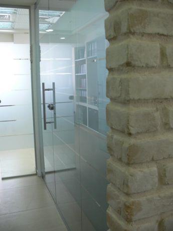 מבואה המשלבת קיר בריקים חשוף ודלתות זכוכית. עיצוב: סיגלית פרץ