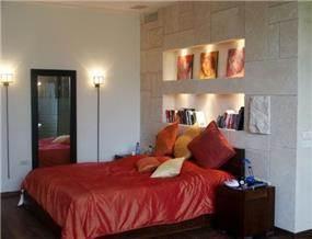 קיר מחופה אבן ונישות גבס בחדר שינה בעיצוב יעל דיילס בכר