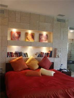 קיר מחופה אבן ונישות גבס עם תאורה בחדר שינה.