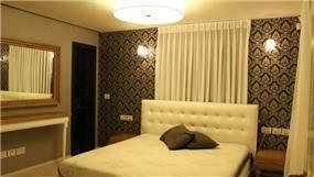 חדר שינה בגווני אפור ולבן עם שילוב של עץ אגוז, עיצוב mind אדריכלים