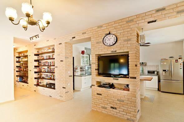 מבט מחלל המגורים לכיוון המטבח. קירות בריקים מייצרים אווירה כפרית. עיצוב: מעשה בבית