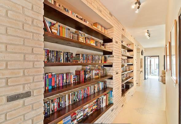 ספריה הבנויה בתוך קירות בריקים שיוצרים אווירה חמימה ומזמינה. עיצוב: מעשה בבית