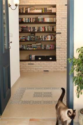 מבואת כניסה לבית שכוללת ספרייה עצומה ודומיננטית. עיצוב: מעשה בבית