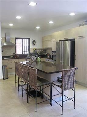 מטבח בסגנון מודרני הכולל גם אי גדול לישיבה, עבודה ואחסון. עיצוב: סטודיו סגול