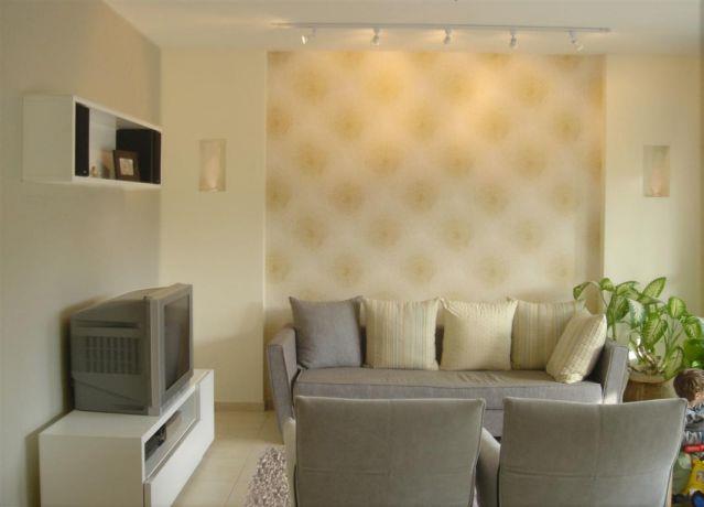 הטפט בגב הספה מודגש בין עמודי גבס ותאורה בעיצוב מיכל גרינברג פוקס