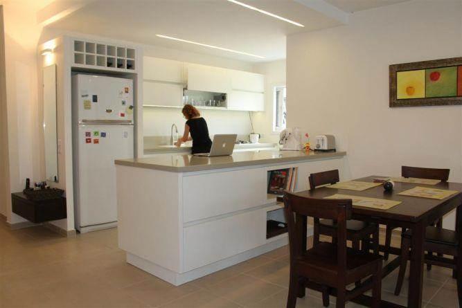 הפרדה באמצעות אי ותאורה בין המטבח לפינת האוכל והסלון בעיצוב מיכל גרינברג פוקס