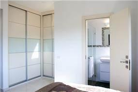 מבט לעבר פינת הארונות וחדר הרחצה בחדר שינה הורים, KanDesign