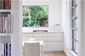 מבט שונה למטבח מעוצב בקווים נקיים על טהרת הצבע הלבן בתכנון ועיצוב של איציק ניב