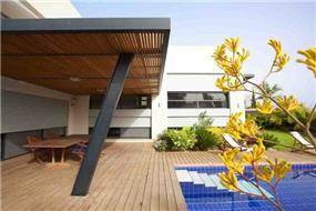 חזית אחורית לבית פרטי, כולל פרגולה, דק ובריכת שחיה בתכנון ועיצוב של איציק ניב