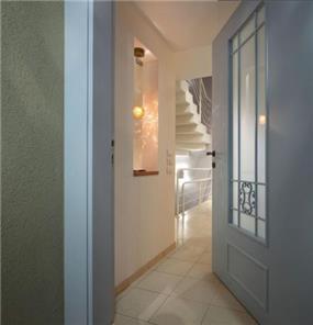 מבט לכניסה לבית בדגש על תאורת מבואה מיוחדת בגומחת גבס בעיצוב ותכנון של נגה ארנסון