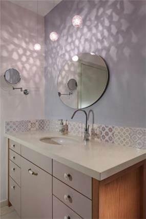 מבט לחדר אמבט מעוצב עם תאורה נתלית מיוחדת המוסיפה אווירה נעימה לחלל בעיצוב ותכנון של נגה ארנסון