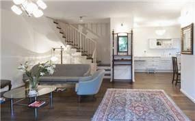 מבט אל הסלון והמטבח בקוטג' בן שלושה מפלסים בבית דגן - תכנון וביצוע ע''י הילה לוסקי