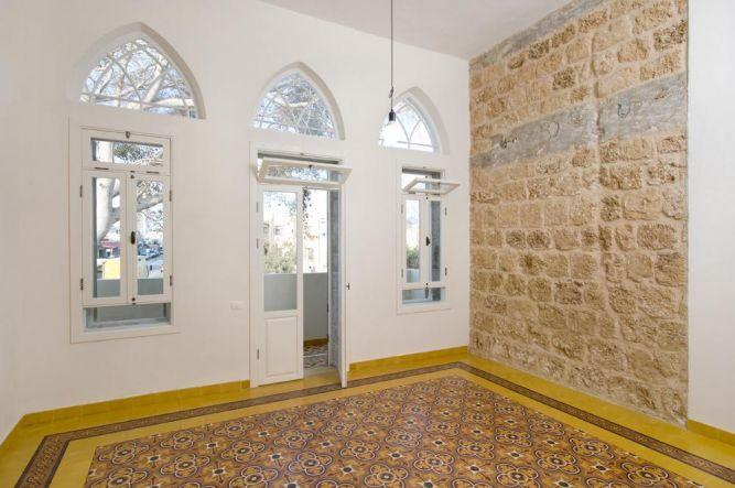 בניין לשימור ביפו חלל המגורים שוחזר, קיר הכורכר נחשף בחלקו. הרצפה המצוירת חלקה משוחזרת וחלקה חדשה.