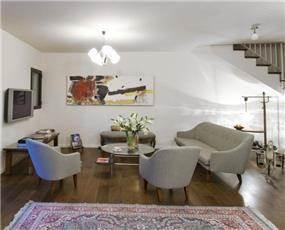 מבט לסלון מהכניסה - רהיטי וינטג' משוק הפשפשים הריצפה מחופה בעץ אלון מגוון בתכנון הילה לוסקי