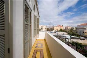 מבט למרפסת חיצונית מעוצבת בעלת חיפוי מקורי, בבניין לשימור ביפו.תכנון ועיצוב של הילה לוסקי