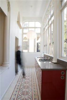 שימור בניין ביפו מבט למטבח מעוצב שמוקם במרפסת סגורה -תכנון ועיצוב הילה לוסקי
