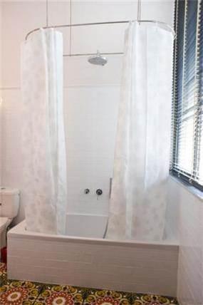 חדר אמבטיה ביחידת הורים עם וילון תלוי מהתקרה בעיצוב ותכנון של הילה לוסקי
