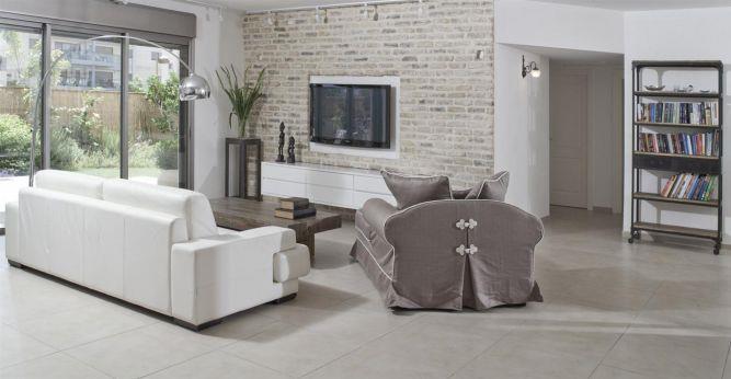 מבט מהסלון המעוצב אל הגינה המקיפה את הבית - עיצוב ותכנון של הילה לוסקי