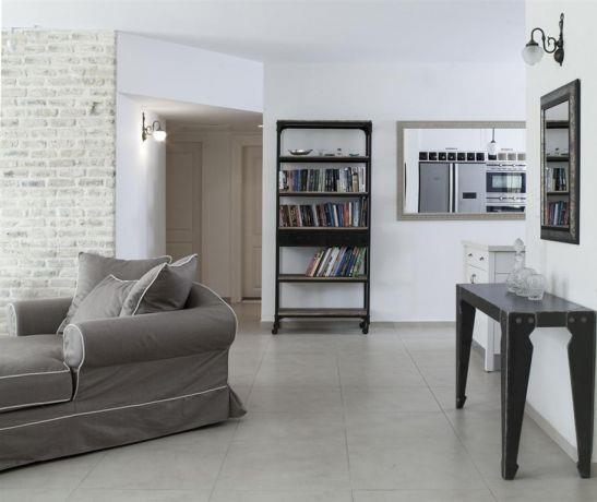 מבט אל חלל הסלון המעוצב ואל המזדרון בבית בקריית אונו בעיצוב ותכנון של הילה לוסקי