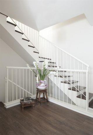 מבט אל גרם המדרגות שנצבע מחדש בלבן, במקום מדרגות השיש הישנות הונחו משטחי עץ אלון על המדרך, עיצוב הילה לוסקי