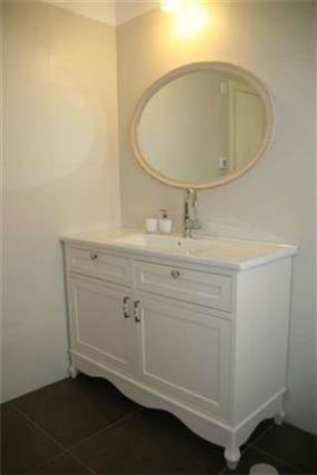 מבט אל חדר אמבטיה בעל מראה גדולה בעיצוב קלאסי נקי של מרב פלגי