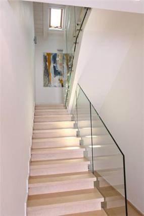 מדרגות עם מעקה זכוכית נקי ללא ידית. עיצוב: סיגל לנמן סוקול
