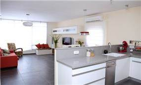 מבט מן המטבח אל הסלון בדירה מעוצבת בסגנון מודרני  - בעיצוב ותכנון של סטודיו קרן רוזנר