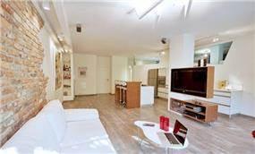 עיצוב דירתו של ליאור סושרד מבט מהסלון עם קיר המחופה בריקים ורצפת פרקט  - בעיצוב ותכנון קרן רוזנר